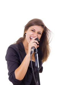 Girl with long hair singing into microphone