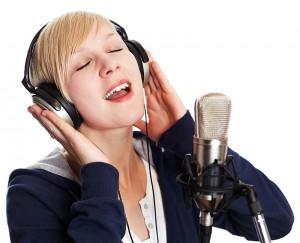 Blond Girl singing with headphones.