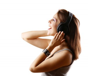 Smiling Girl having singing lessons with headphones.